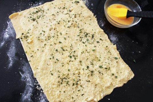 Kaasvlinders: Besprenkel het bladerdeeg met kaas en peterselie